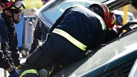Pompieri che lavorano in un salvataggio di incidente di traffico video d archivio