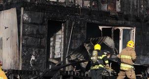 Pompieri che per mezzo del gancio del luccio sul fuoco della casa stock footage
