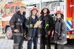 Pompieri che stanno insieme alla caserma dei pompieri immagine stock libera da diritti