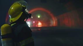 Pompieri dentro un tunnel scuro con le luci di emergenza nei precedenti video d archivio