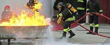 Pompieri durante l'esercizio di allenamento fuori da un fuoco enorme Fotografia Stock Libera da Diritti