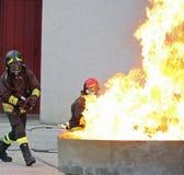 Pompieri durante l'esercizio di allenamento fuori da un fuoco enorme nella b Fotografia Stock