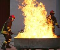 Pompieri durante l'esercizio di allenamento fuori da un fuoco nel brazie Fotografia Stock