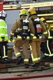 Pompieri in respiratore con l'autopompa antincendio Fotografia Stock