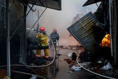 Pompieri su fuoco Il vigile del fuoco estingue il fuoco con acqua Il mercato estero è su fuoco Immagine Stock