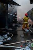Pompieri su fuoco Il vigile del fuoco estingue il fuoco con acqua Il mercato estero è su fuoco fotografia stock libera da diritti