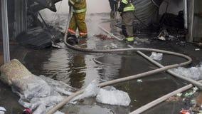 Pompieri su fuoco Il vigile del fuoco estingue il fuoco con acqua Il mercato estero è su fuoco video d archivio