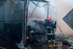 Pompieri su fuoco Il vigile del fuoco estingue il fuoco con acqua Il mercato estero è su fuoco Immagini Stock Libere da Diritti