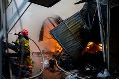 Pompieri su fuoco Il vigile del fuoco estingue il fuoco con acqua Il mercato estero è su fuoco fotografia stock