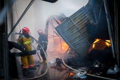 Pompieri su fuoco Il vigile del fuoco estingue il fuoco con acqua Il mercato estero è su fuoco Immagini Stock