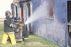 Pompiers éteignant une maison sur l'incendie Image stock