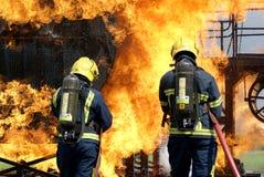 Pompiers combattant le feu image stock