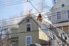 Pompiers combattant le feu de maison image libre de droits