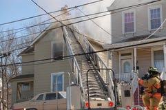 Pompiers combattant le feu de maison photographie stock libre de droits