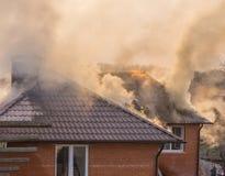 Pompiers combattant un feu faisant rage avec les flammes énormes du timbe brûlant Image libre de droits
