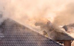 Pompiers combattant un feu faisant rage avec les flammes énormes du timbe brûlant Photo libre de droits