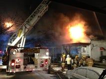 Pompiers luttant le feu de maison Photographie stock libre de droits