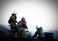 Pompiers sous un formulaire spécial sur le toit d'une maison brûlante images stock