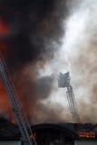 Pompiers sur une grue au-dessus de toit d'incendie Photographie stock libre de droits