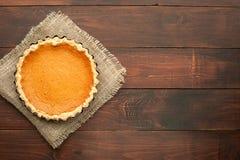 Pompoen eigengemaakte pastei bij houten die achtergrond met voedsel wordt geschikt ing stock foto