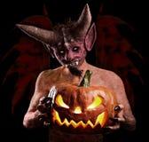 Pompoen Halloween in de handen van de duivel Stock Foto