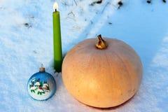 Pompoen, kaars en Kerstboomstuk speelgoed in de sneeuw Stock Afbeelding
