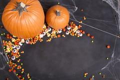 Pompoenen en Halloween-suikergoed over een zwart bord wordt verspreid dat stock foto's