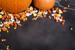 Pompoenen en Halloween-suikergoed over een zwart bord wordt verspreid dat stock afbeeldingen