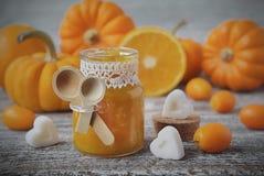 Pompoenjam met sinaasappelen op een uitstekende houten lijst Stock Foto's