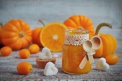 Pompoenjam met sinaasappelen op een uitstekende houten lijst Royalty-vrije Stock Foto
