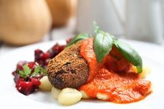 Pompoenkoteletten met tomatensaus op bollen op gnocchi, geroosterde bietensalade worden gediend die stock afbeeldingen
