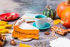 Pompoenpastei die met suikerglazuursuiker wordt bestrooid met een kop van koffie royalty-vrije stock afbeelding