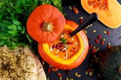 Pompoensoep met zaden, gojibessen, peterselie en knoflook vlak brood voor de herfstdiner Royalty-vrije Stock Afbeeldingen