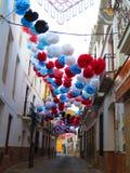 Pompoms de papel coloridos suspendidos sobre a rua da vila Fotos de Stock Royalty Free