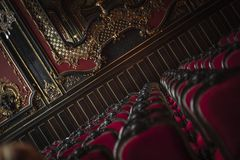 A pompous concert room, slanting recorded. A slanting record of a pompous concert hall in the style of renaissance with upholstered red chairs in the foreground Stock Photos