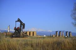 Pompowy Jack szyb naftowy z Tęsk Szczytowy i cysternowy gospodarstwo rolne obraz royalty free