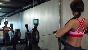 Pompująca dziewczyna ćwiczenia na wioślarskiej maszynie zbiory