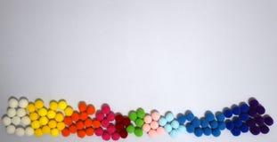 Poms dulces dispuestos del pom del color de la pendiente en el fondo blanco imagen de archivo libre de regalías