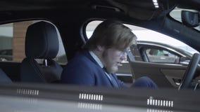 Pomyślny zadawalający brodaty biznesmen w szkłach i garniturze dostaje w samochodzie Przedstawicielstwo firmy samochodowej zbiory wideo