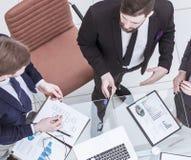 Pomyślna biznes drużyna dyskutuje marketingowego plan blisko nowożytnego miejsca pracy zdjęcia stock