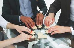 Pomyślna biznes drużyna składa kawałki łamigłówki obsiadanie za biurkiem fotografia royalty free