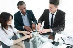 Pomyślna biznes drużyna składa kawałki łamigłówki obsiadanie za biurkiem zdjęcia stock