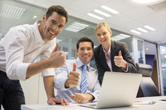 Pomyślna biznes drużyna w biurze, przyglądająca kamera, daje thum Obraz Royalty Free