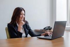Pomyślna biznesowa kobieta pracuje przy biurem zdjęcia royalty free