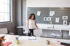 Pomyślna biznesowa kobieta stoi w jej biurze fotografia stock