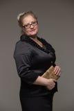 Pomyślna biznesowa kobieta wiek średni z rzemiennym sprzęgłem wewnątrz zdjęcia stock