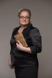Pomyślna biznesowa kobieta wiek średni z rzemiennym sprzęgłem wewnątrz zdjęcia royalty free