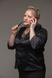 Pomyślna biznesowa w średnim wieku kobieta opowiada na th z szkłami obrazy royalty free