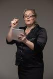 Pomyślna biznesowa w średnim wieku kobieta pisze w notatnika impor zdjęcia stock