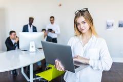 Pomyślna biznesowej kobiety pozycja z laptopem z jej personelem w tle przy nowożytnym jaskrawym biurem obraz royalty free